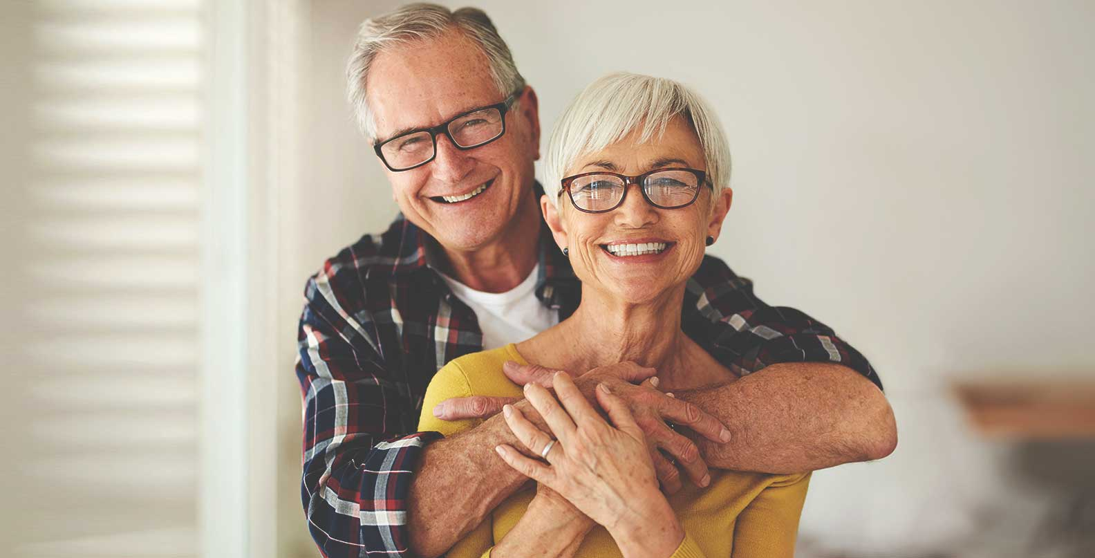 older couple hug smiling 1