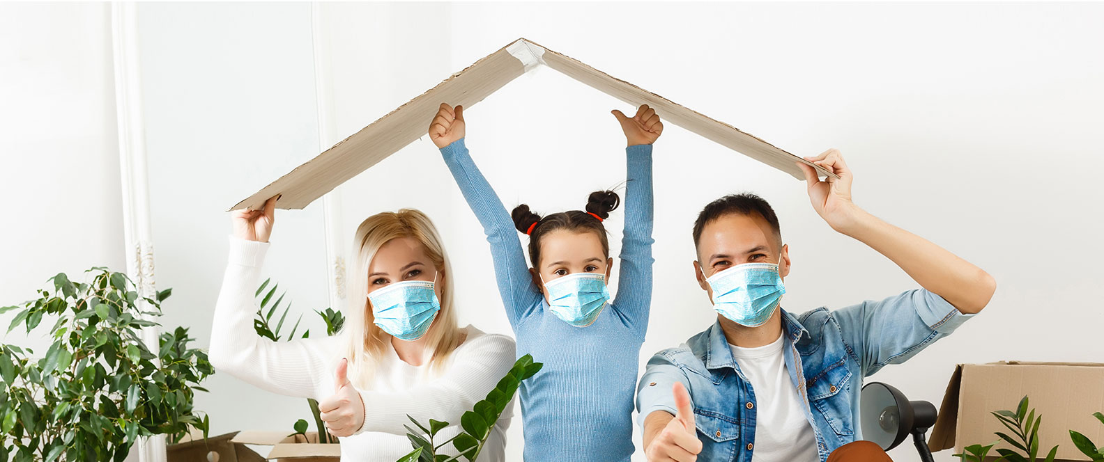 family with mask carrying cardboard house roof